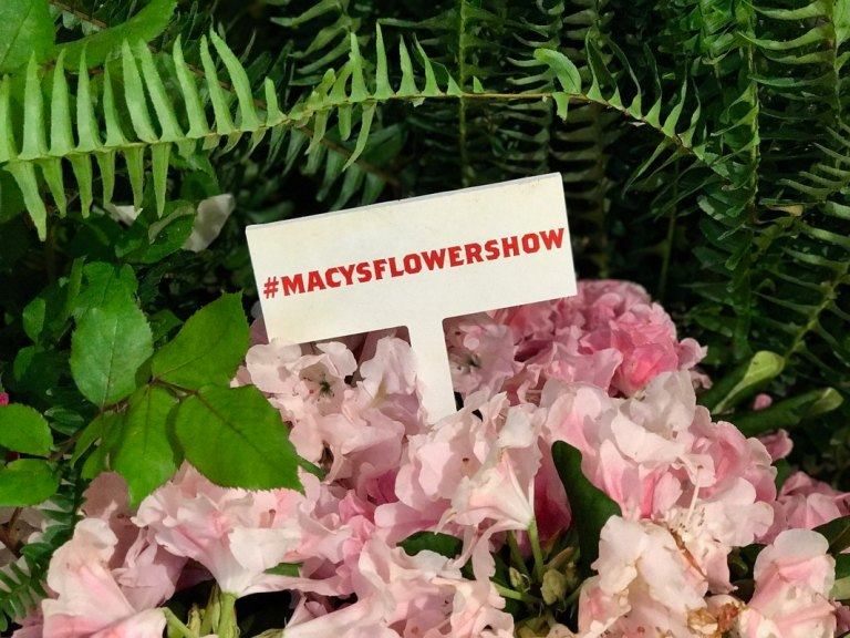 Macy's Flower Show hashtag sign with flowers